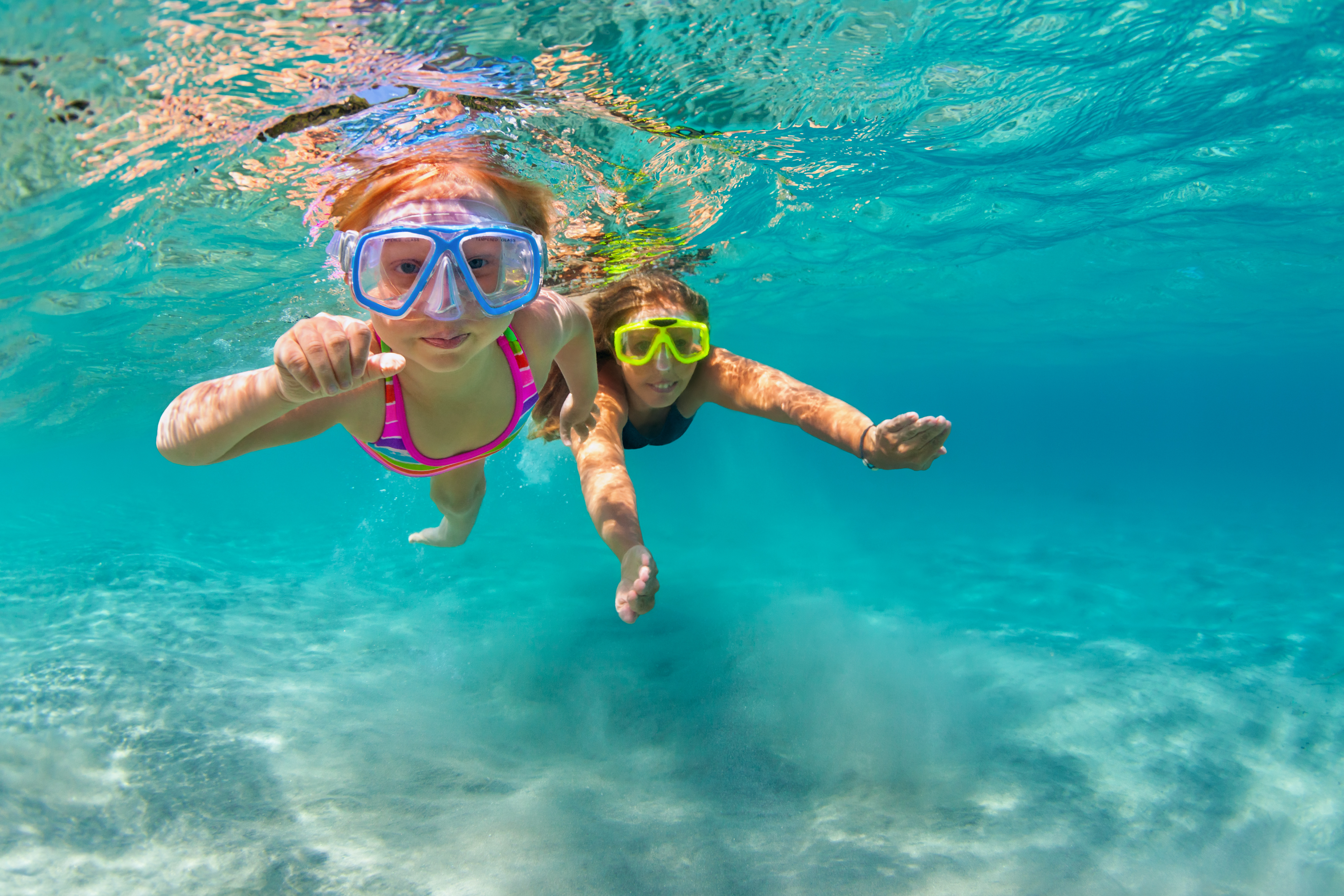 Mother with child swim underwater with fun in sea