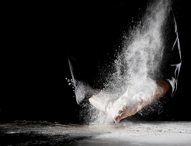 Cloud of flour spraying into air as man rubs hands